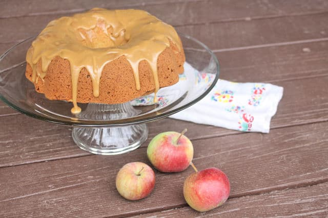 Apple cake with caramel glaze on a cake plate with fresh apples.