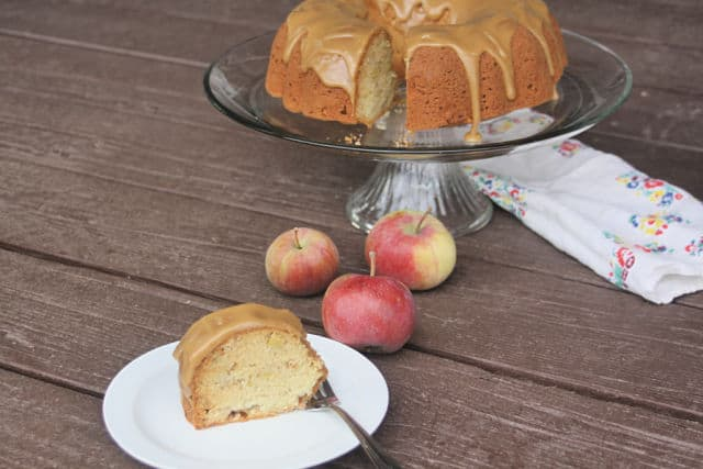 A slice of easy apple cake with caramel glaze on a plate in front of whole cake with fresh apples and a napkin.