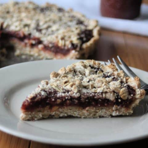 A slice of gluten-free jam tart on a plate with a fork.