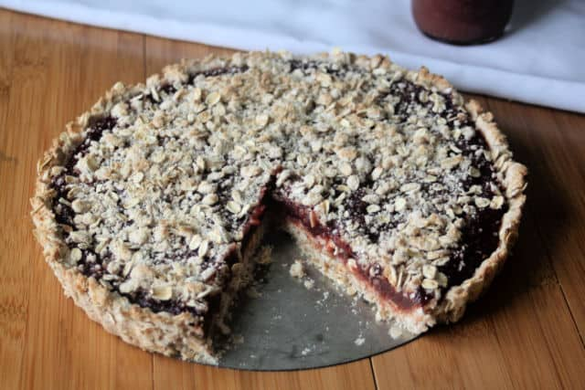 A gluten-free jam tart with piece missing on a table.