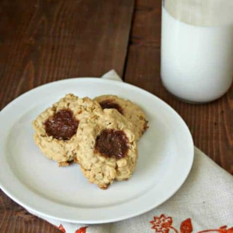 Peanut Butter and Jelly Thumbprint cookies on a plate with a glass of milk.