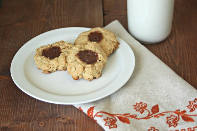 Peanut butter and jelly thumbprint cookies on a plate with a glass of milk