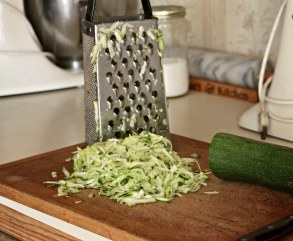 Grating zucchini on a box grater.