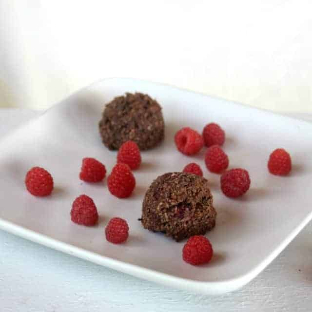 Chocolate Raspberry Coconut Macaroons on a plate with fresh raspberries
