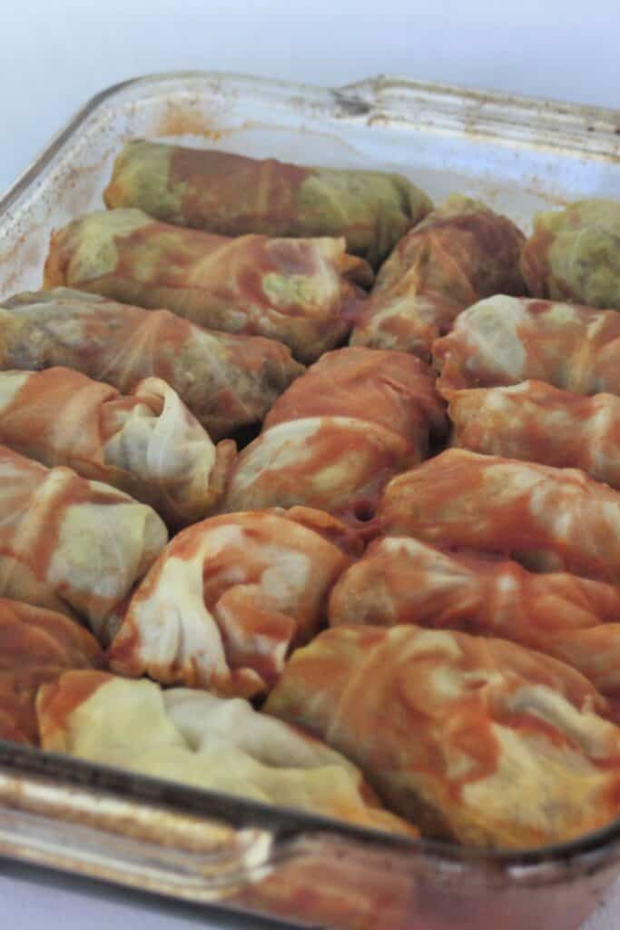 A glass baking tray full of cooked cabbage rolls covered in tomato juice.
