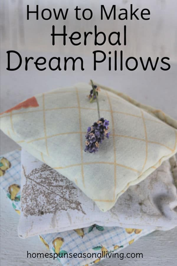 A stack of herbal dream pillows with fresh lavender on top.