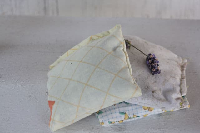 On herbal dream pillow leaning on a stack of 2 dream pillows topped with fresh lavender flower.