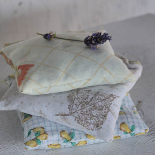 A stack of herbal dream pillows on a table with a sprig of lavender sitting on top.