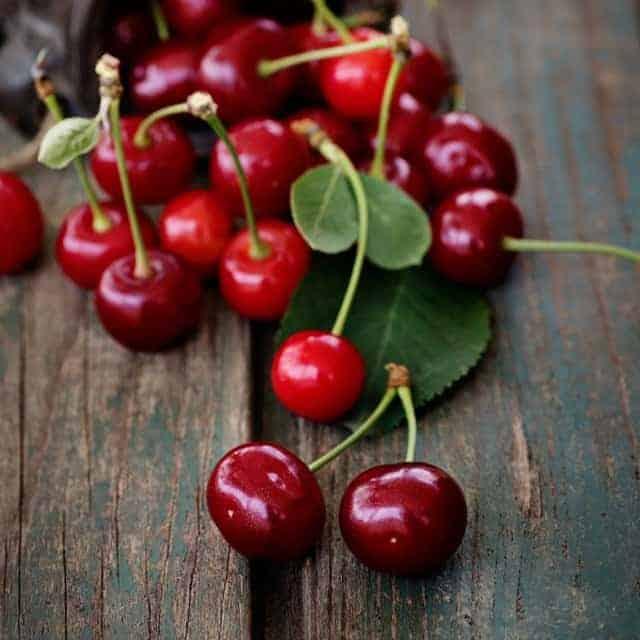 Sweet cherries on a wooden board.