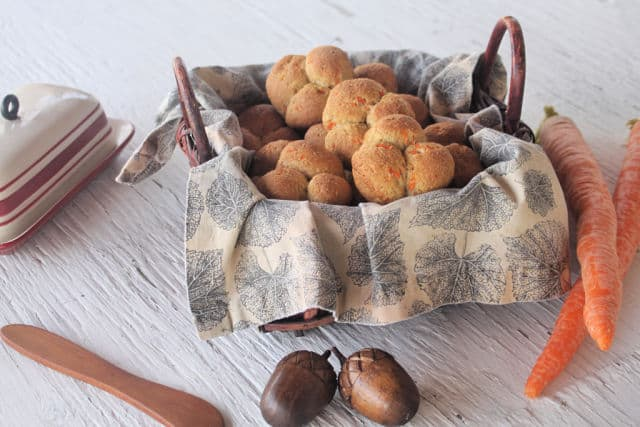 Carrot cloverleaf rolls in a napkin lined basket with a butter dish and knife.