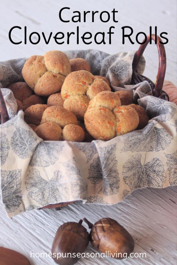 Carrot cloverleaf rolls in a napkin lined basket.