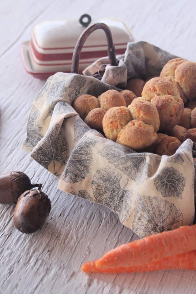 Carrot cloverleaf rolls in a napkin lined basket with a butter dish and carrots.