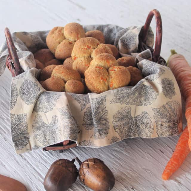 Carrot cloverleaf rolls in a napkin lined basket