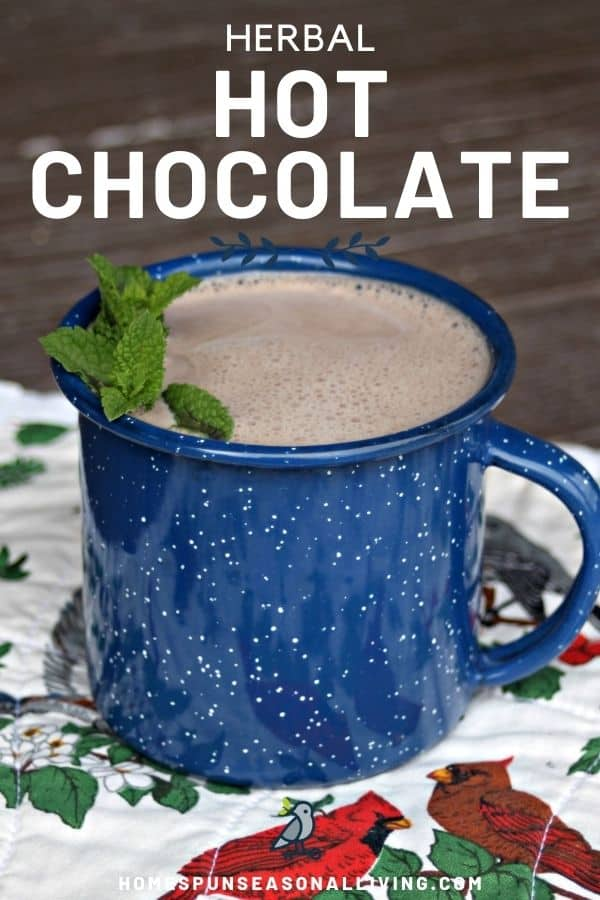 A blue tin cup full of hot chocolate decorated with fresh sprigs of mint sitting on a floral and bird covered placemat with text overlay reading herbal hot chocolate.