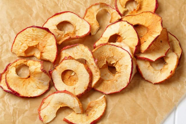 Dried apple slices on a board.