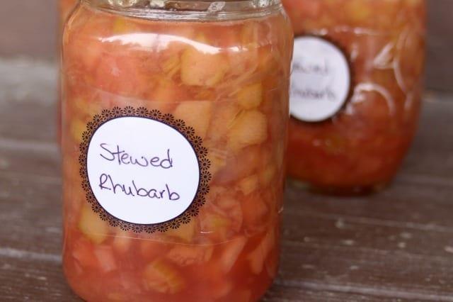 Jars of labeled stewed rhubarb on a wood table.