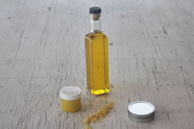Strained dandelion oil in a clear bottle surrounded by containers of balms and beeswax.