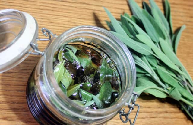 Jar of sage leaves infusing honey.