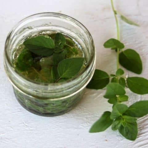 Oregano leaves infusing in a jar of honey.