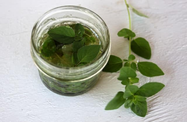 Oregano leaves infusing in a jar of honey.