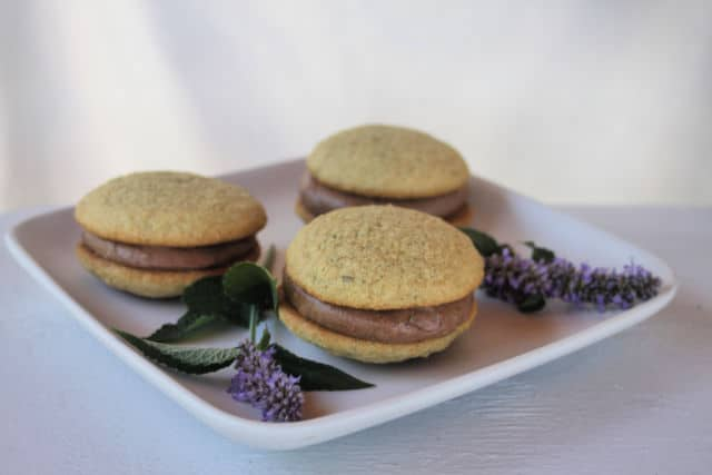 Anise hyssop whoopie pies on a plate with sprigs of fresh anise hyssop.