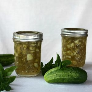 Jars of cucumber mint jam on a table with whole cucumbers and fresh mint.