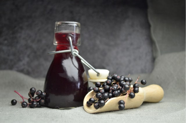Elderberry tincture in an open bottle surrounded by a wooden scoop and fresh elderberries.