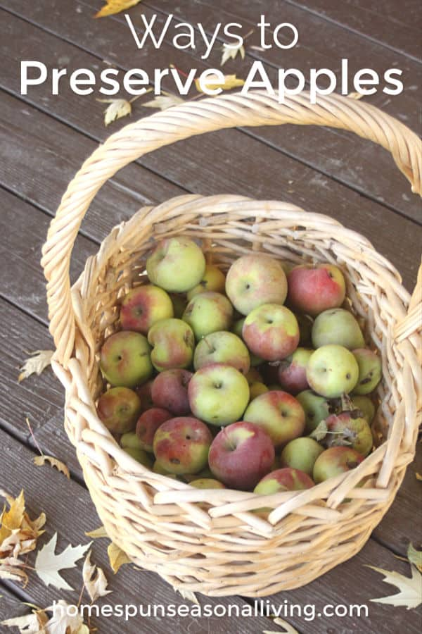 Apples in a basket surrounded by fall leaves.