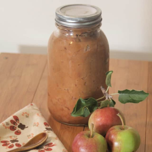 A jar of chunky applesauce on a table with fresh apples, a napkin, and a spoon.