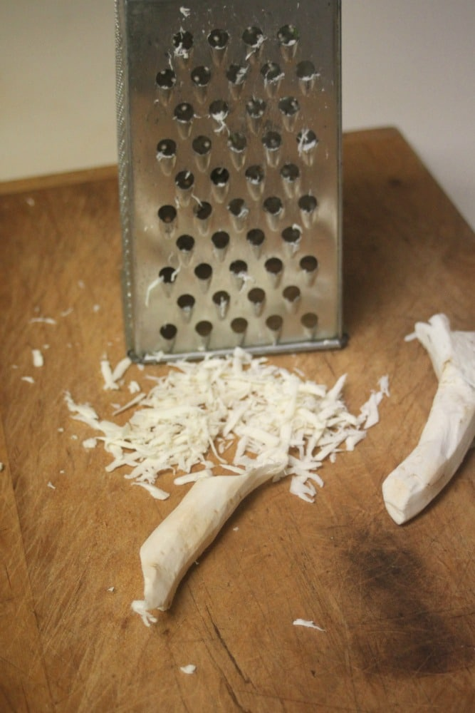 Grated horseradish root sitting on wooden cutting board next to box grater and pieces of whole root.