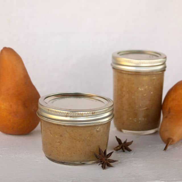 Jars of pear butter with whole pears and spices.