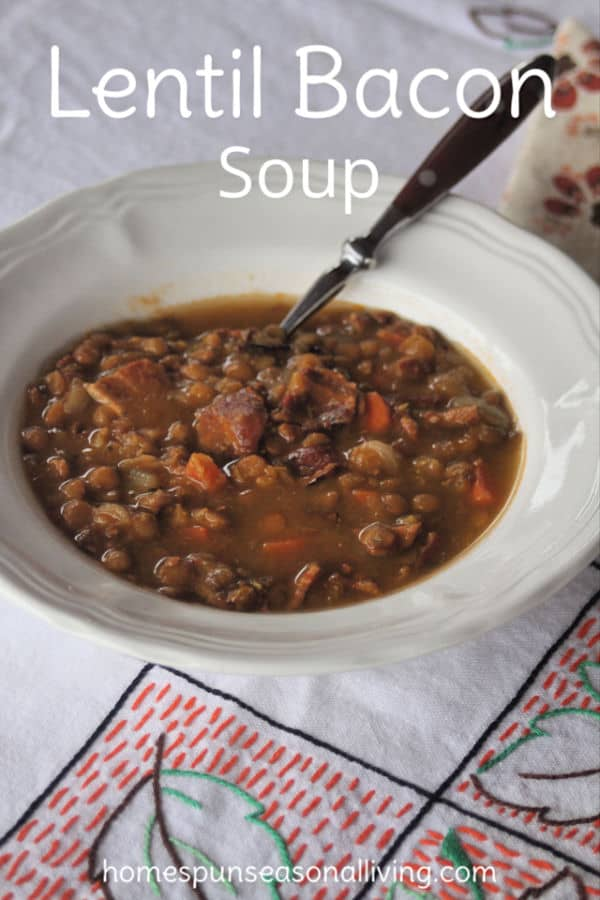 A bowl of lentil bacon soup with a spoon siting on a tablecloth.