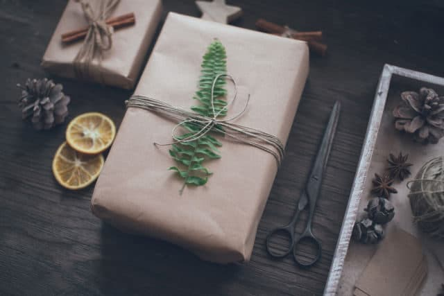 A gift wrapped in brown paper with a leaf and twine surrounded by dried fruit and spices.