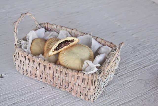 Rum raisin filled cookies stacked in a basket.