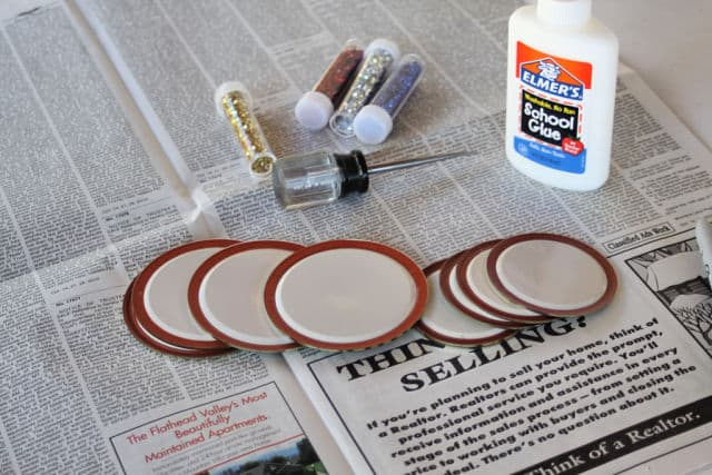 Canning lids, glue, an awl, and glitter spread out on newspaper to make upcycled canning lid gift tags.