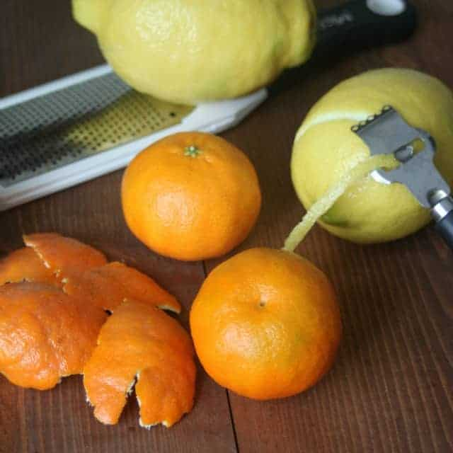 Mandarin oranges and lemons sitting on a table with a peeler and grater.