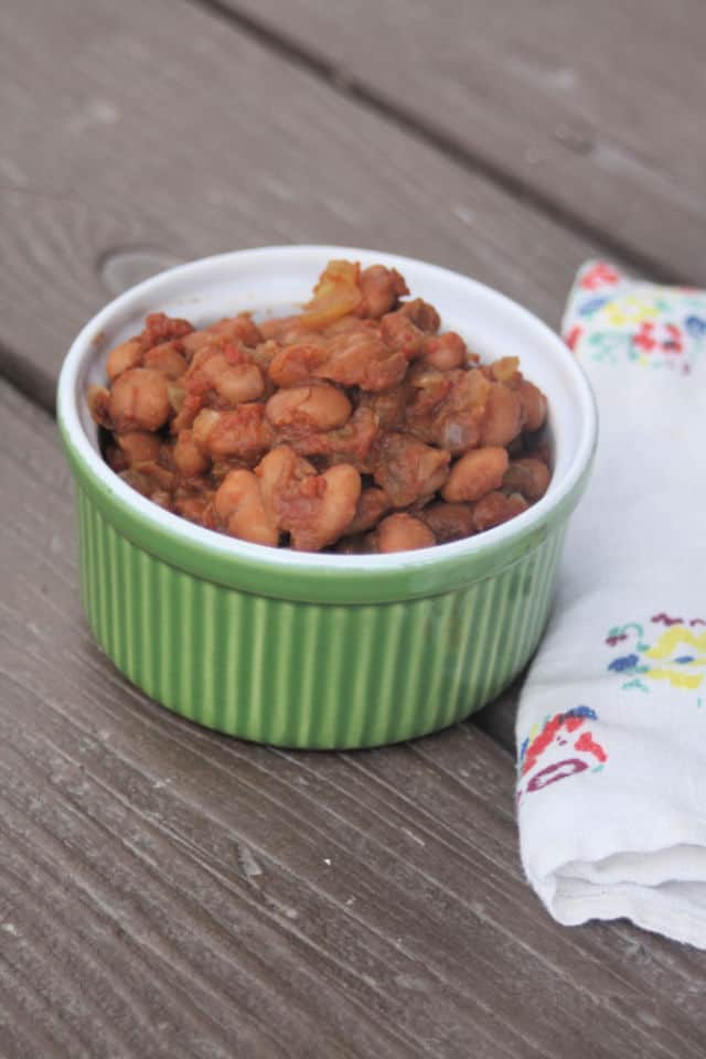 A bowl of baked beans with napkin.