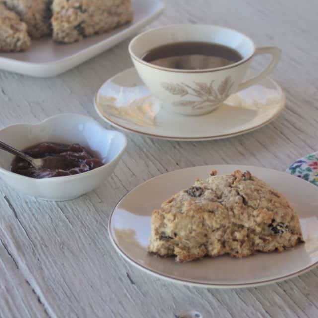 A maple muesli scone on a plate with a bowl of jam and cup of tea on a table.