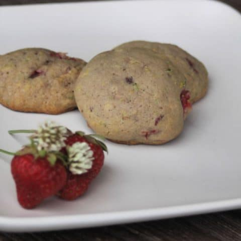 3 strawberry white clover cookies on a plate with fresh strawberries and white clover blossoms.