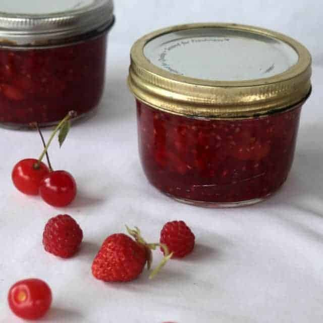 Jars of brandied cherry berry preserves on a table with fresh berries and cherries.