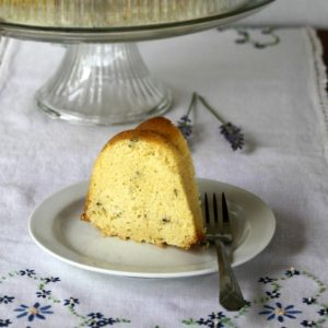 Slice of lavender bundt cake on a cloth covered table.