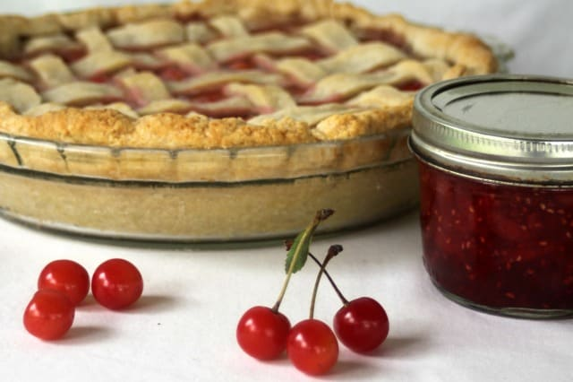 Sour cherry pie with jam and raw cherries on table.