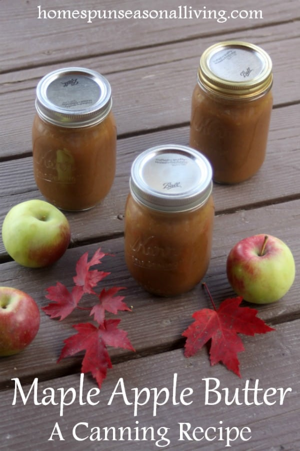 3 jars of maple apple butter on wooden boards with fresh apples and red maple leaves.