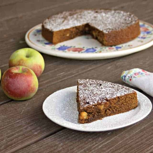 A slice of apple molasses cake on a plate.