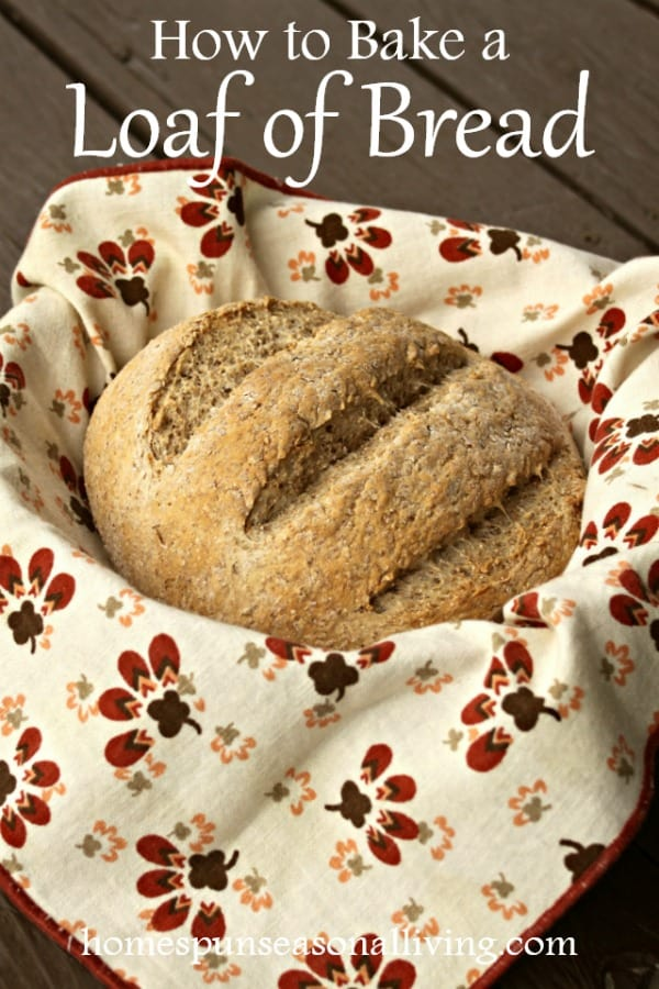 A round loaf of bread in a napkin lined basket.