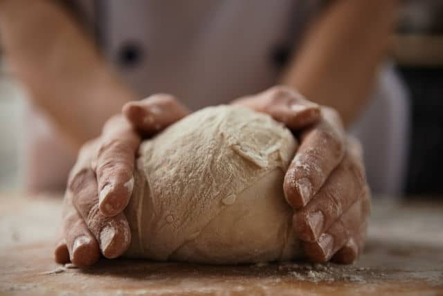 Hands kneading bread dough on a board.