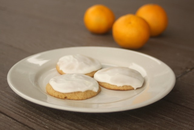 3 frosted orange cookies on a white plate with 2 fresh oranges in the background.
