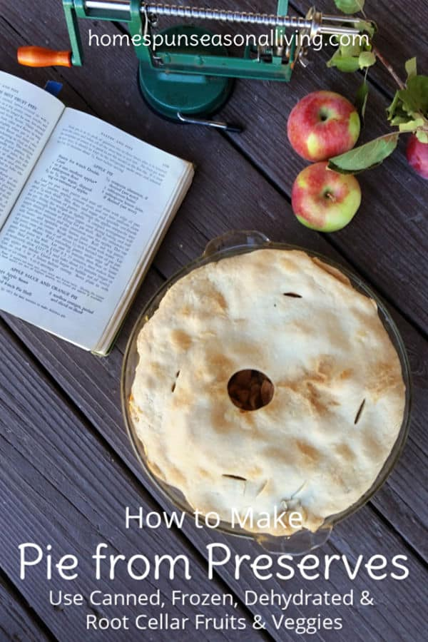 Apple pie on a table with cookbook and fresh apples.