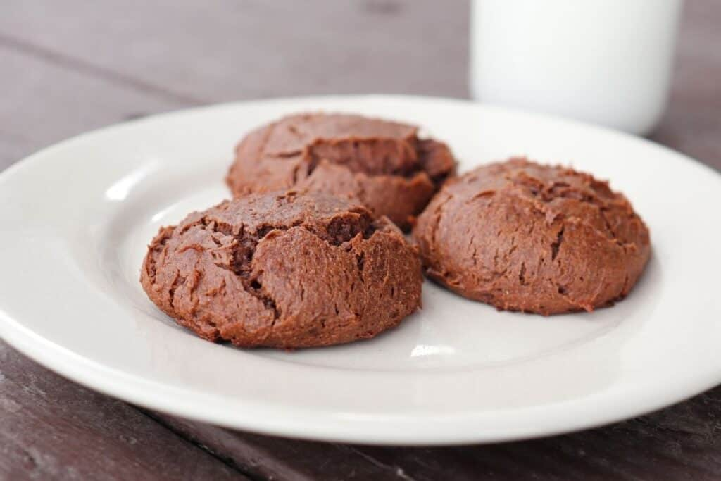 3 chocolate cheesecakes cookies on a white plate with a glass of milk in the background.