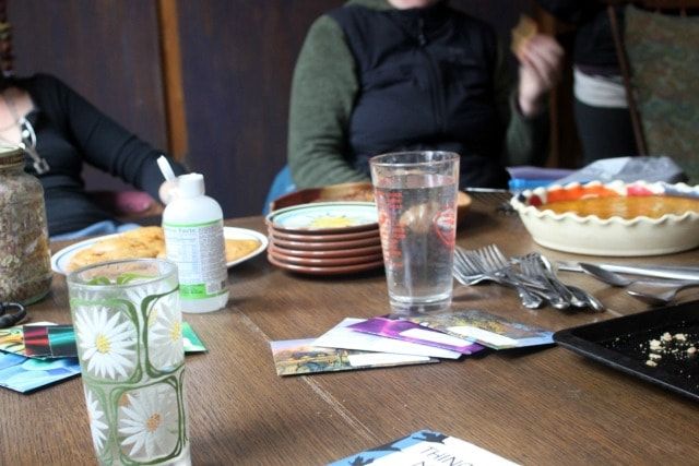 A table with water glasses, envelopes, and people talking.